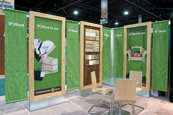 Graphics panels are flanked with hanging cloth banners unfurling the brand's green woodgrain design. Wood-framed panel equipped with peg system holds removable product samples.